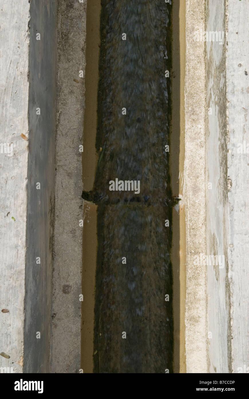 L'eau qui coule dans une évacuation d'eau pluviales Photo Stock