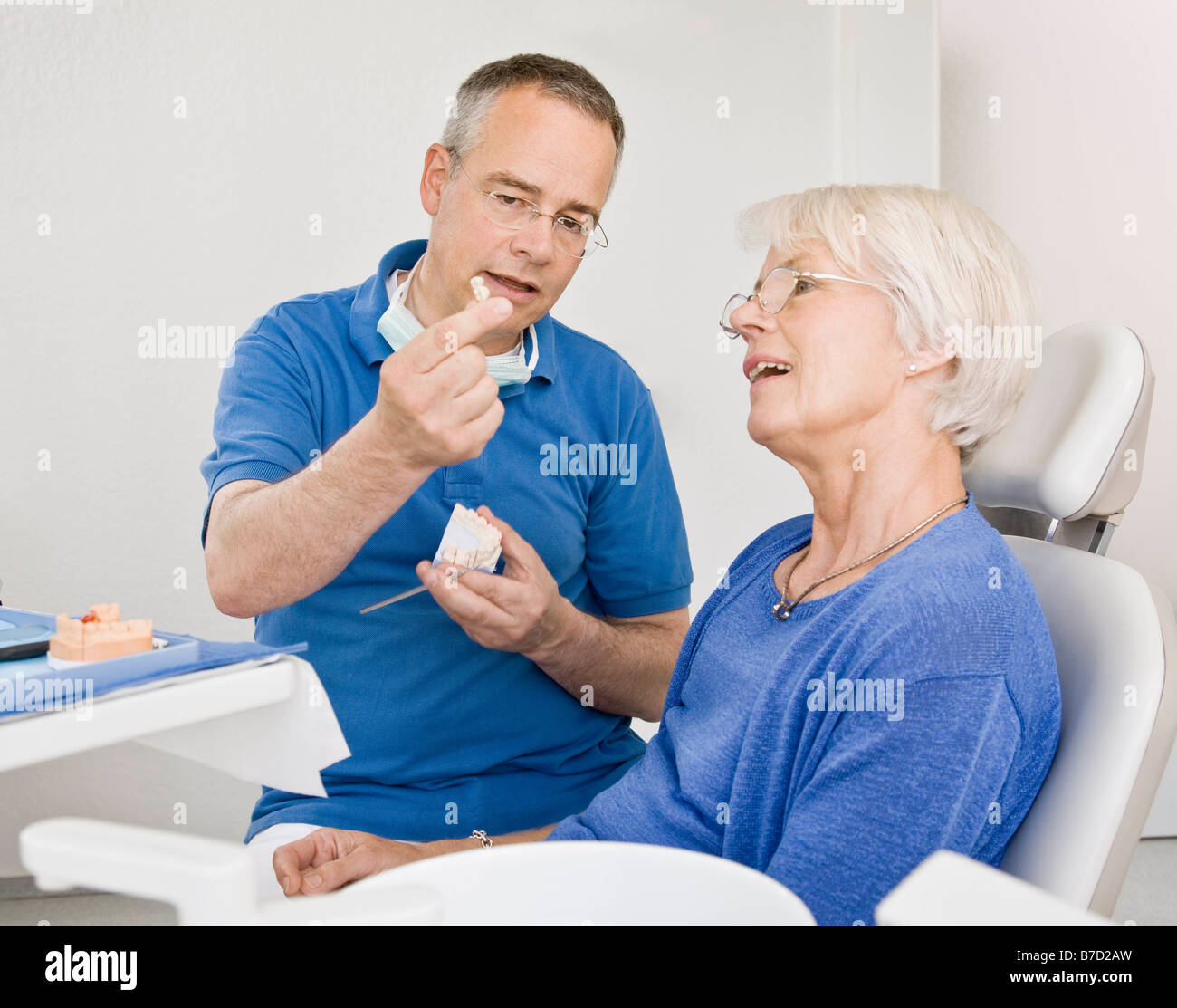 Male dentist talking with female patient Photo Stock