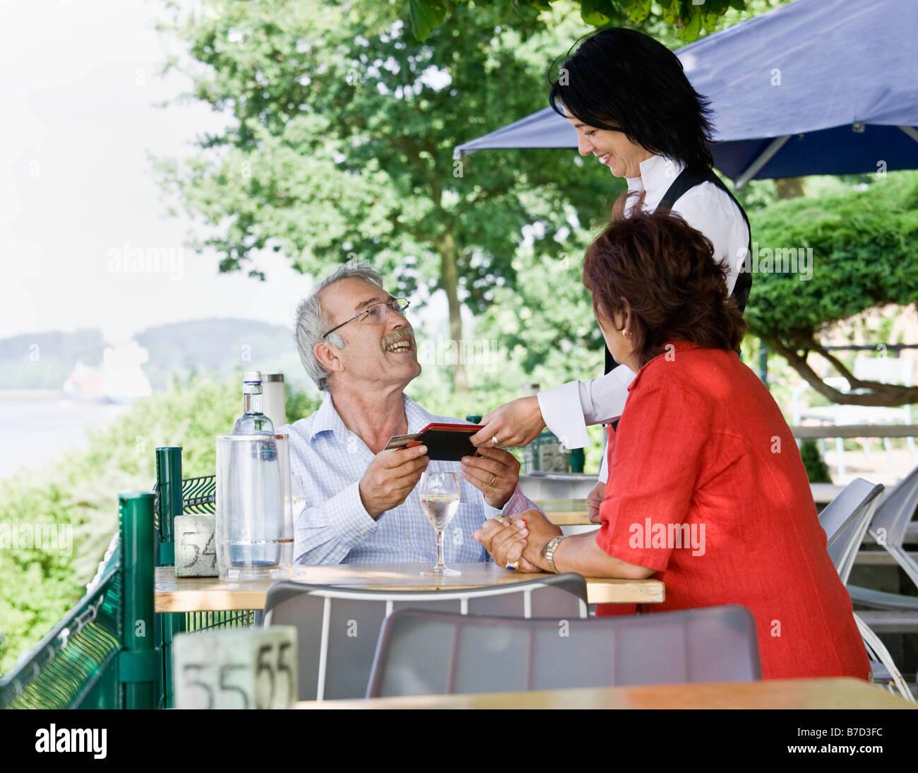 Serveuse ce qui porte le projet de loi à la table Photo Stock