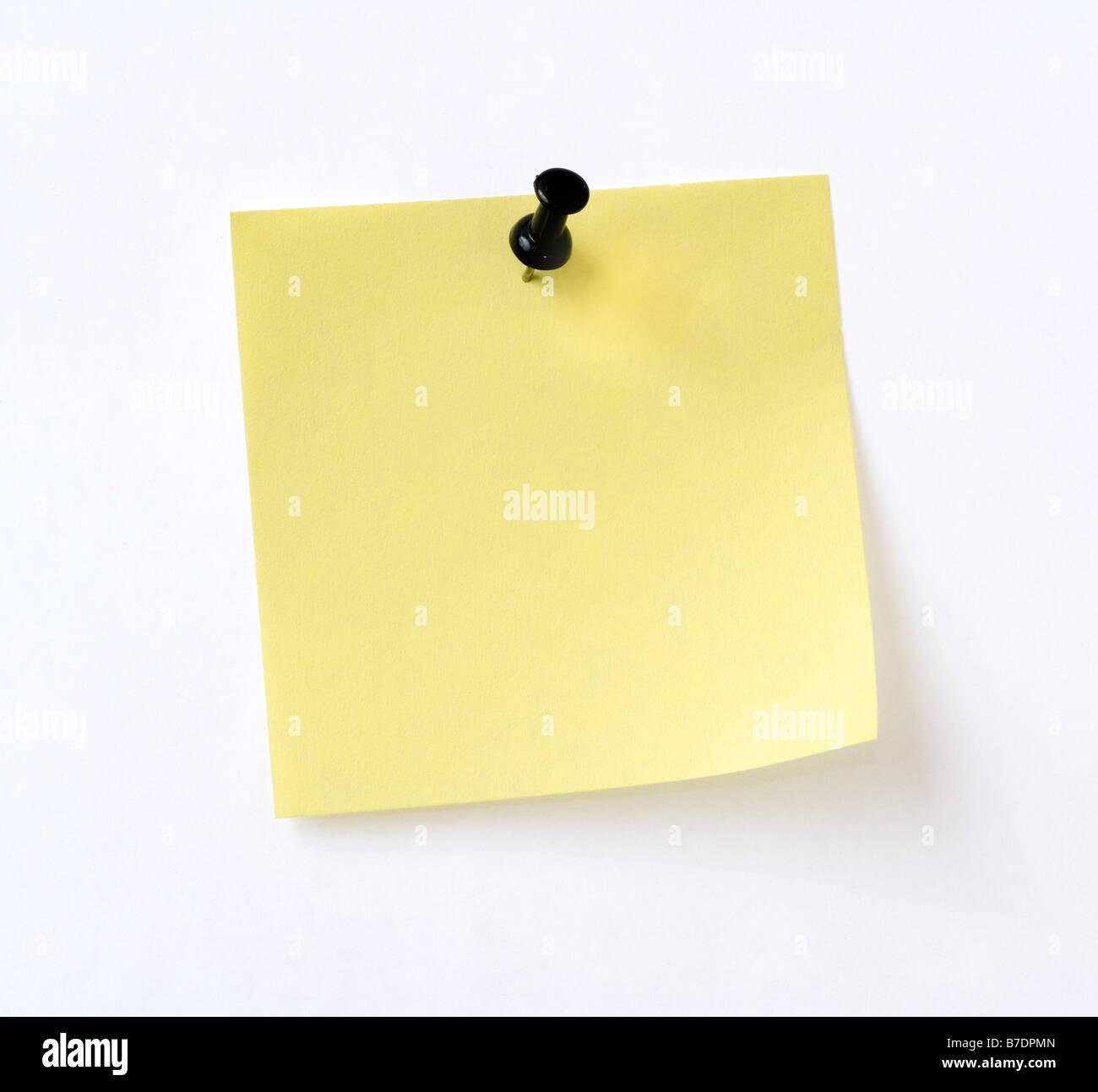 Note jaune avec broche noire sur fond blanc Photo Stock