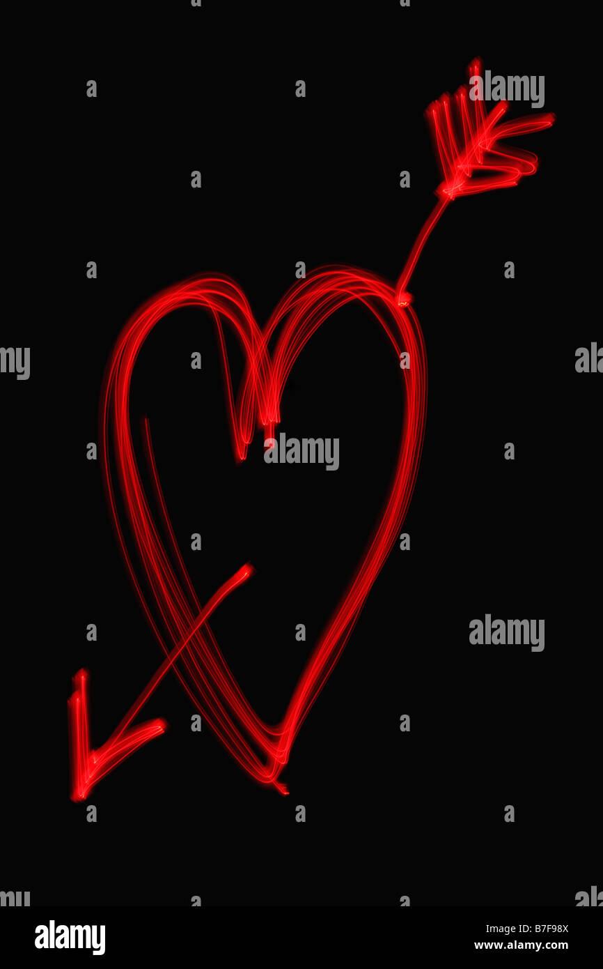 Peinture de lumière d'un cœur rouge avec une flèche à travers elle Banque D'Images