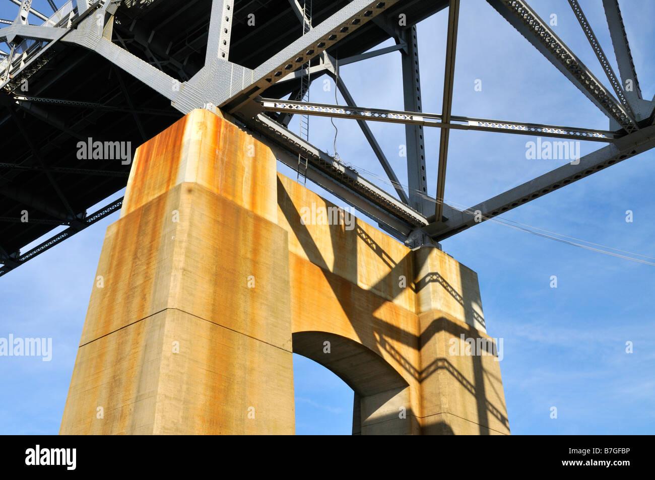 Levant les yeux de sous un pont montrant l'appui concret des poutres d'acier et bleu ciel Photo Stock
