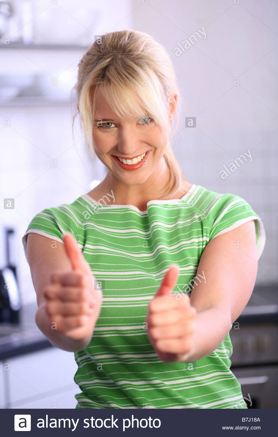 Portrait of young blonde woman giving Thumbs up Photo Stock