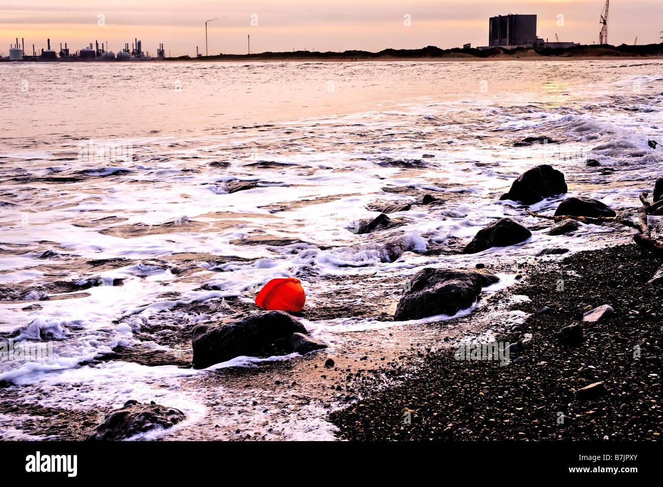 Construction Worker's hard hat lavé à terre avec l'industrie et Teeside centrale nucléaire Photo Stock