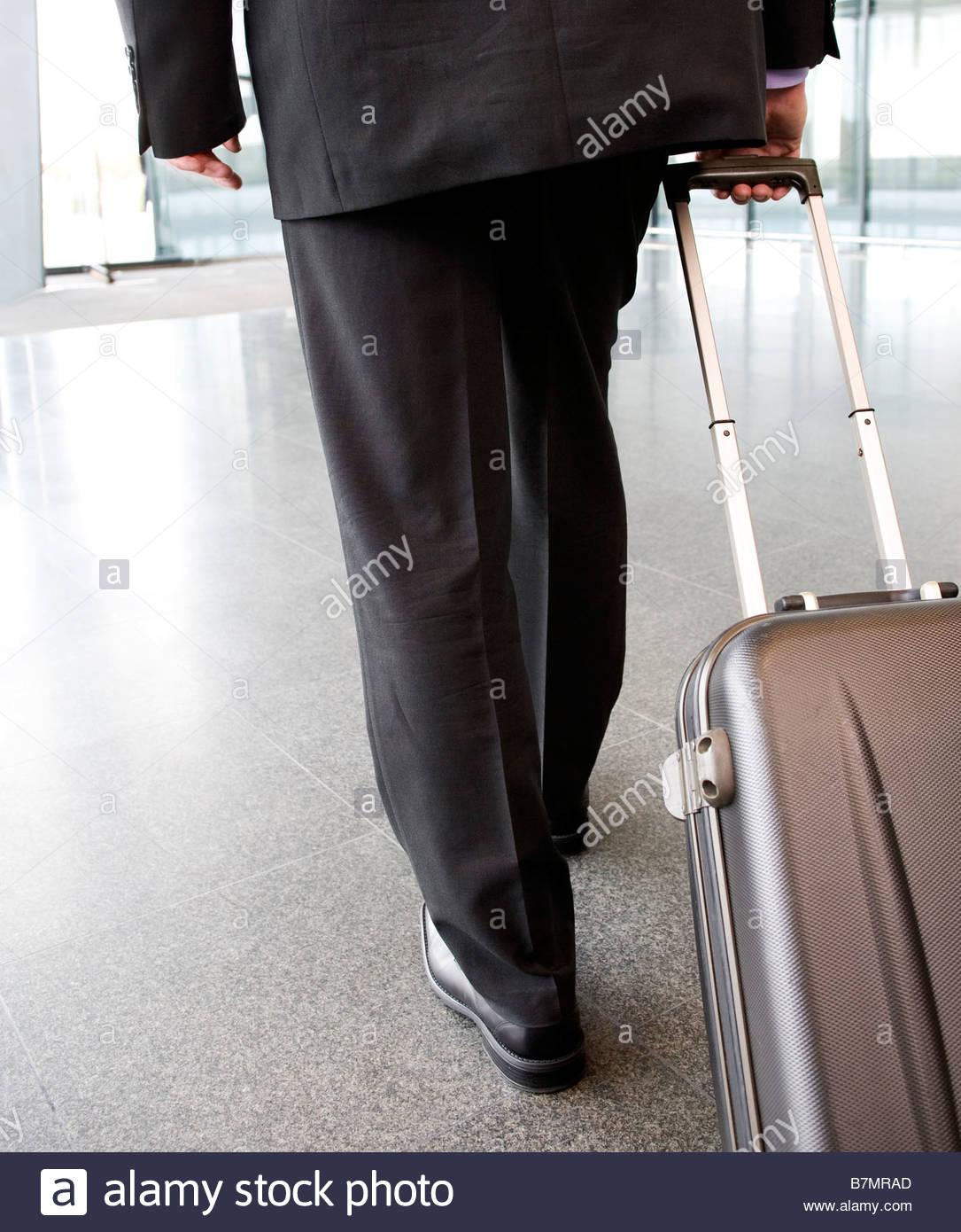 Un businessman pulling suitcase le long Photo Stock