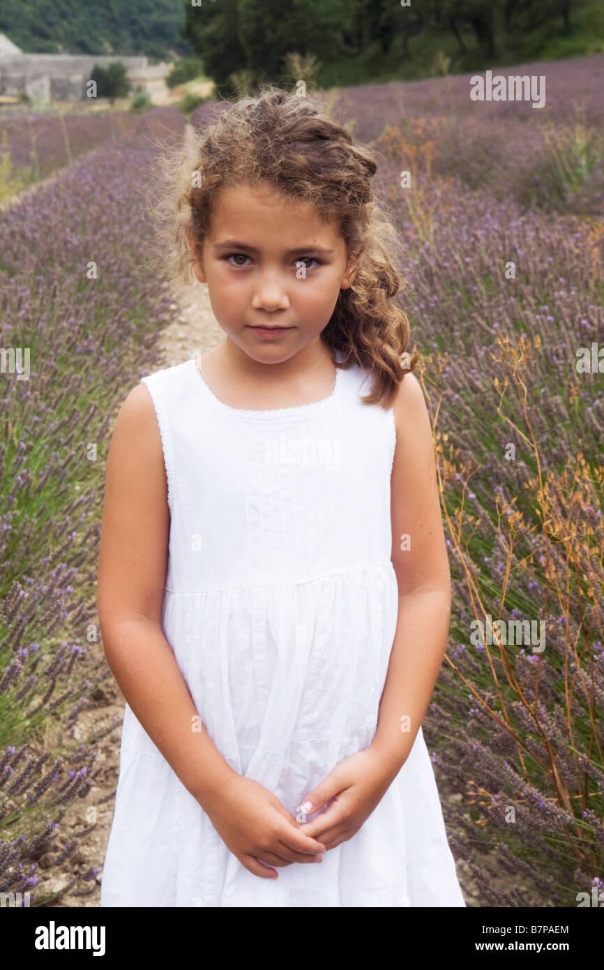 Beau 8 ans, fille, debout dans un champ de lavande avec l'abbaye de Sénanque en arrière-plan, Gordes, Photo Stock