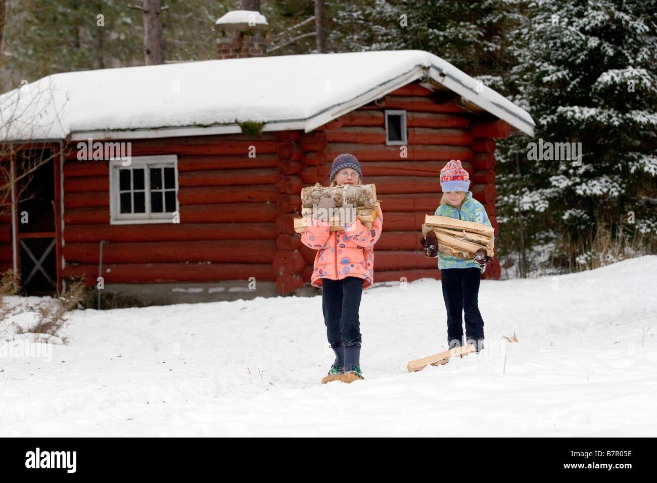 Deux jeunes filles en raquettes transporter le bois dans la neige hiver Ely Minnesota Photo Stock