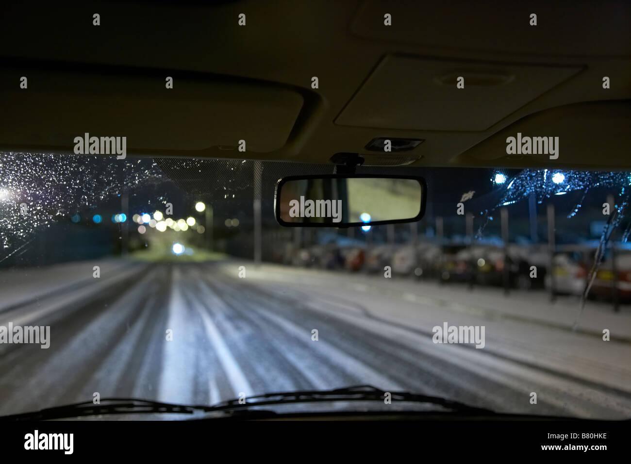 voiture roulant sur une route enneigée vide la nuit à l'intérieur le royaume-uni Banque D'Images