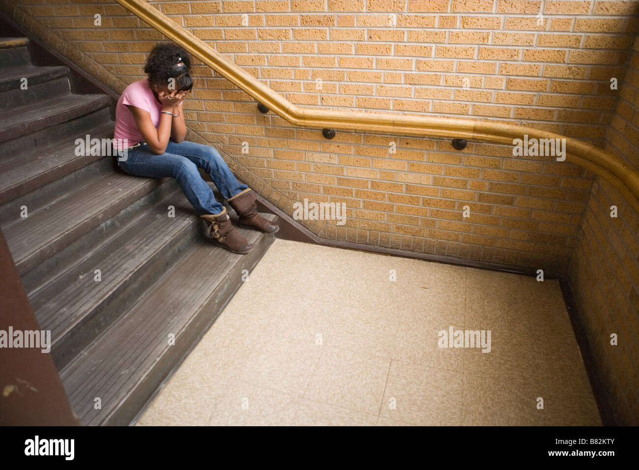 Teenage african american girl de pleurer sur l'escalier à l'école, assis sur l'étape Photo Stock