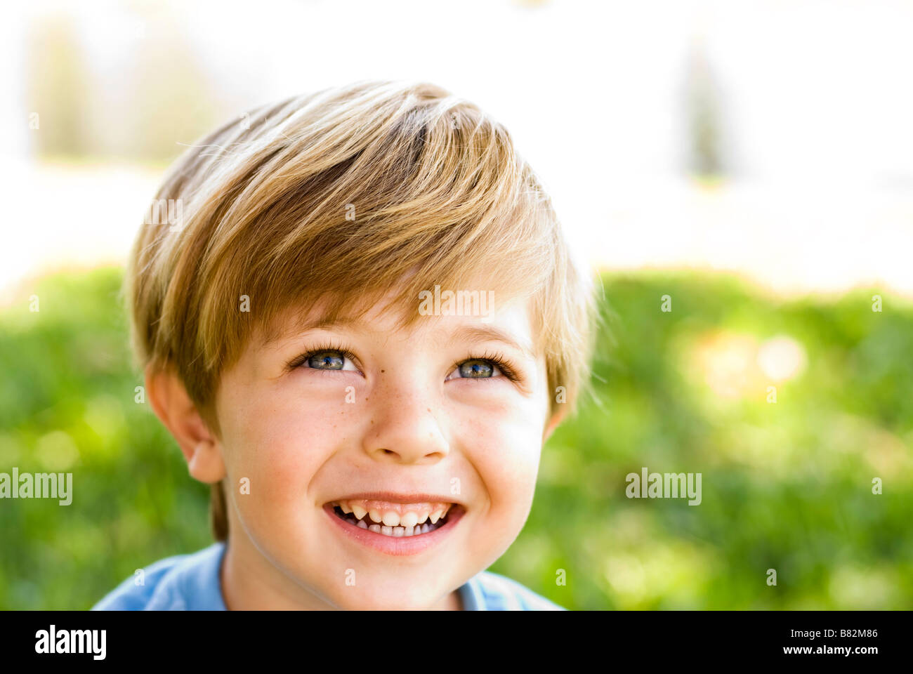 Boy laughing outdoors jouant Photo Stock