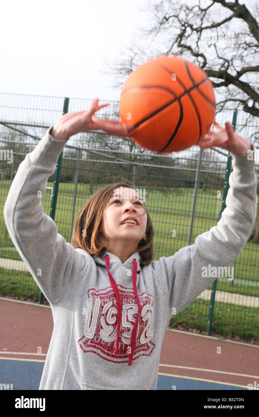 Teenage girl practicing netball dans un parc Photo Stock
