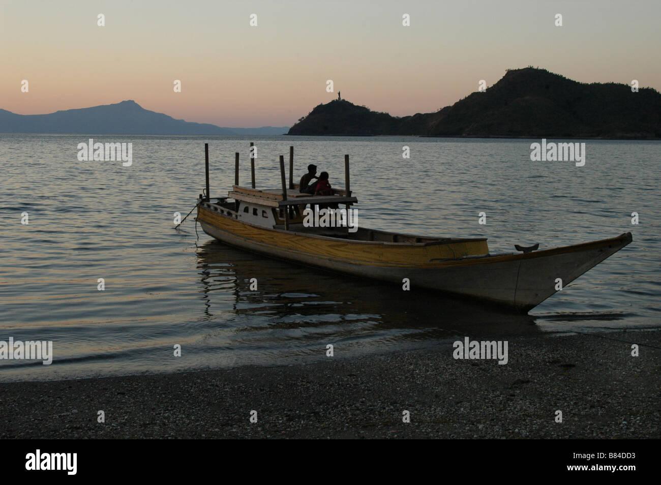 Un bateau amarré sur le port de Dili au Timor Leste avec la silhouette d'Azur Fatucama Banque D'Images