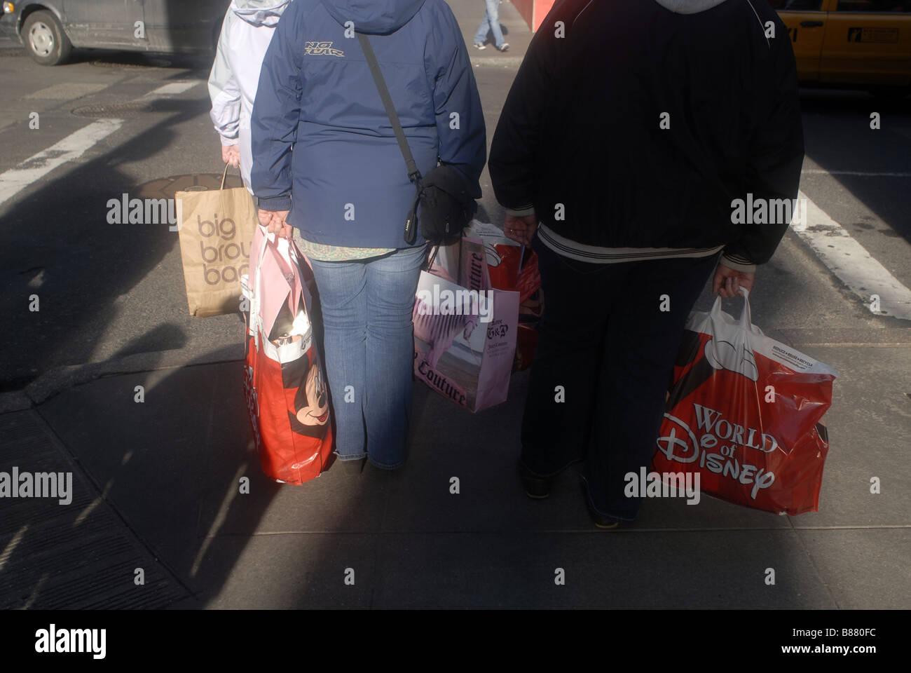 Les touristes avec leurs achats à New York Photo Stock