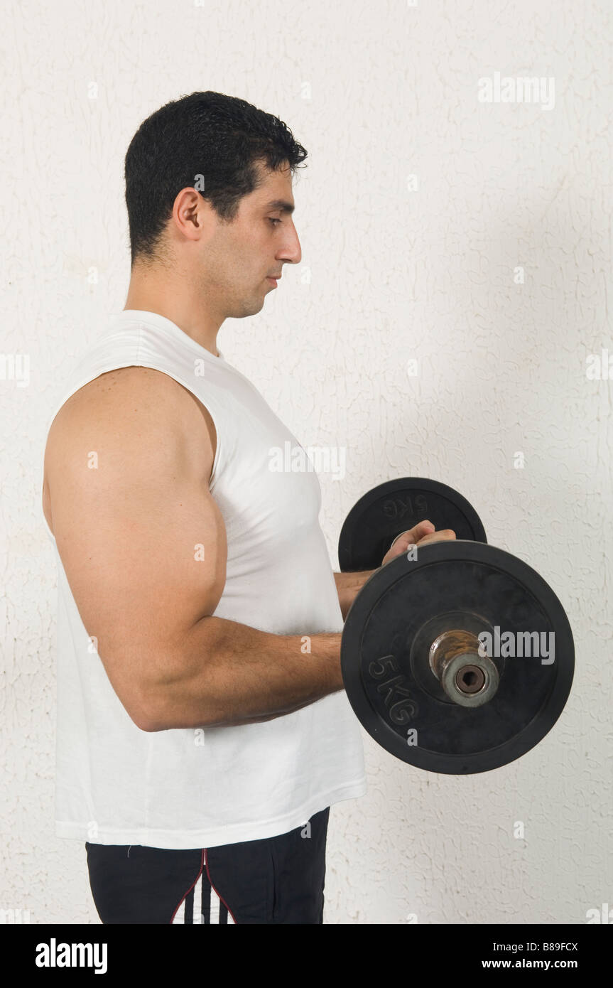 Man training biceps dans la salle de sport Photo Stock