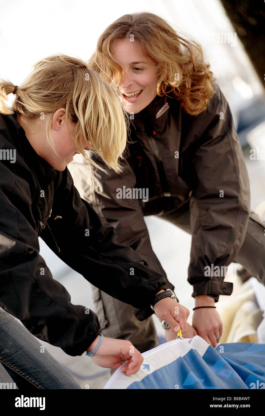 2 femmes marins préparant le gréement pour un voyage,la femme de 20 à 30 sont en âge et s'esclaffent. Photo Stock