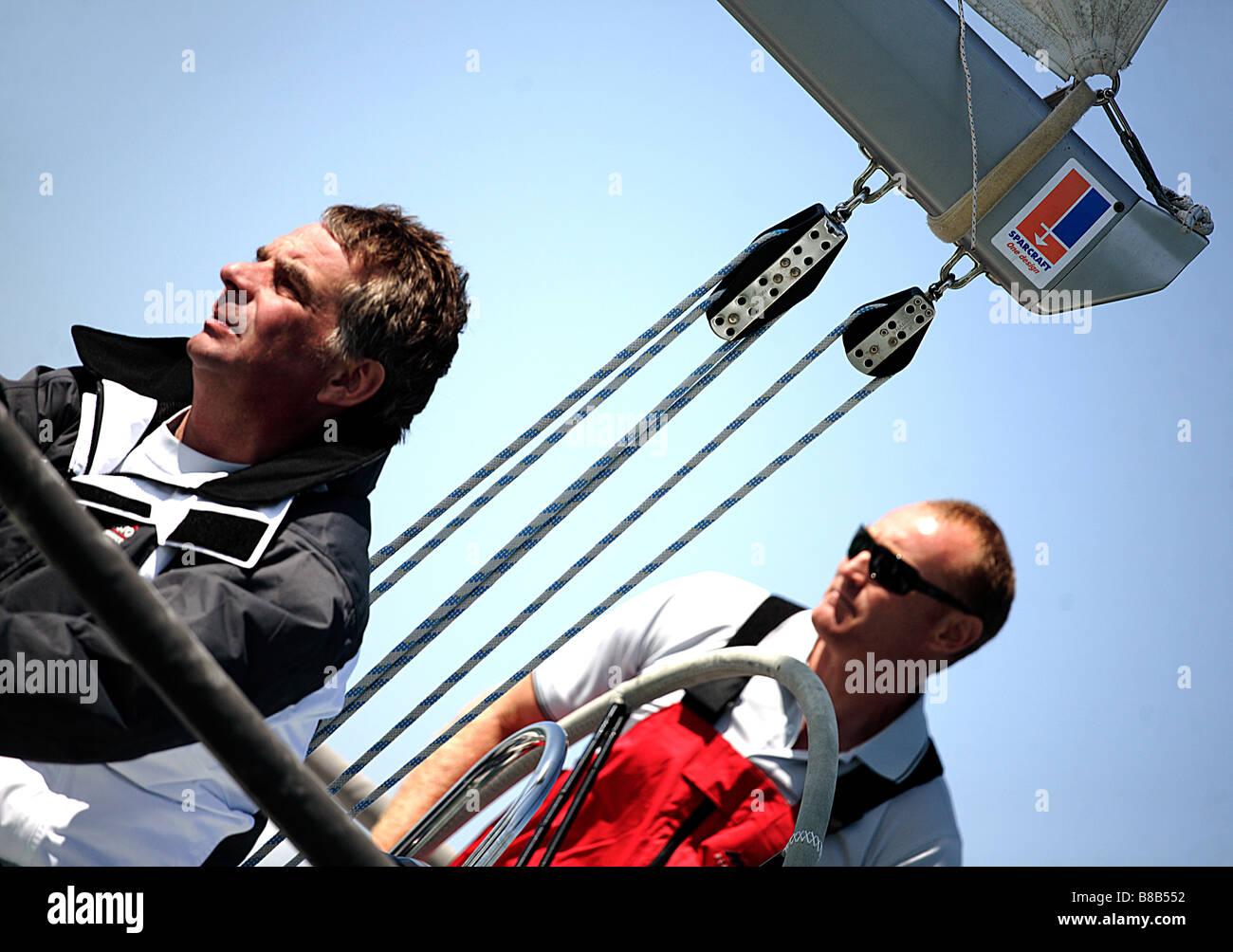 2 hommes,europe,un yacht à voile blanc,il dispose de gréement et est tourné à un angle lw. Banque D'Images