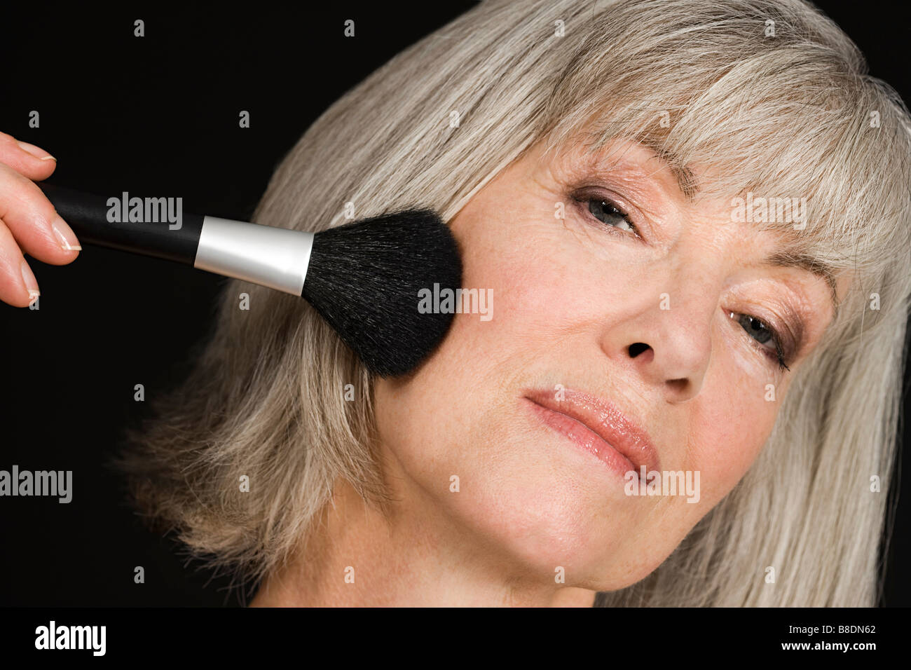 Senior woman applying make up Banque D'Images