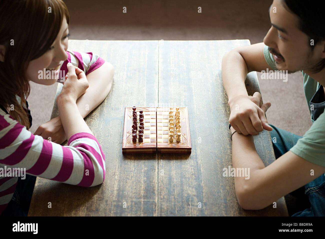 Jeune couple jouant aux échecs Photo Stock