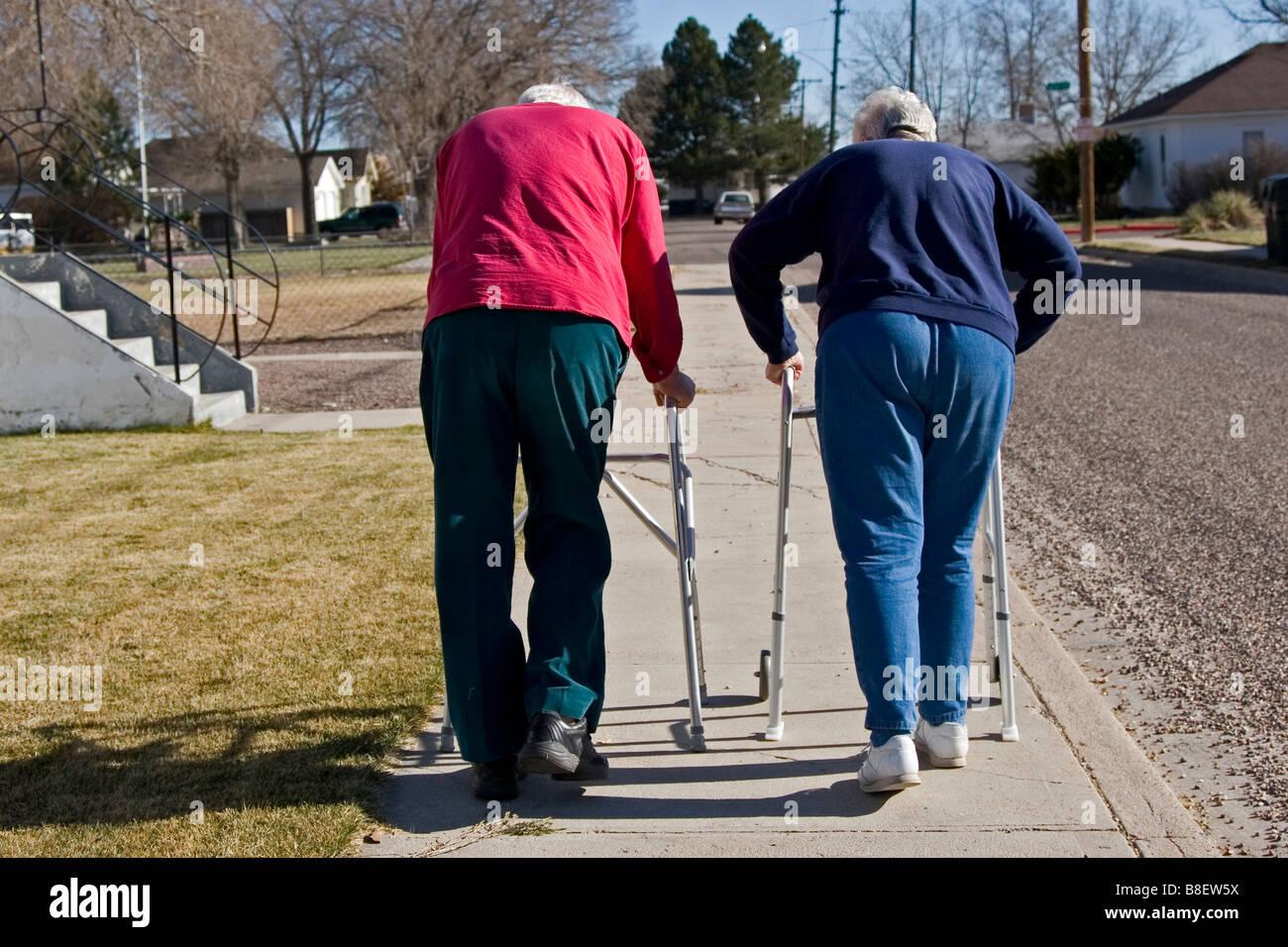 Deux personnes âgées personnes âgées à pied à l'aide de marcheurs, l'un des Photo Stock