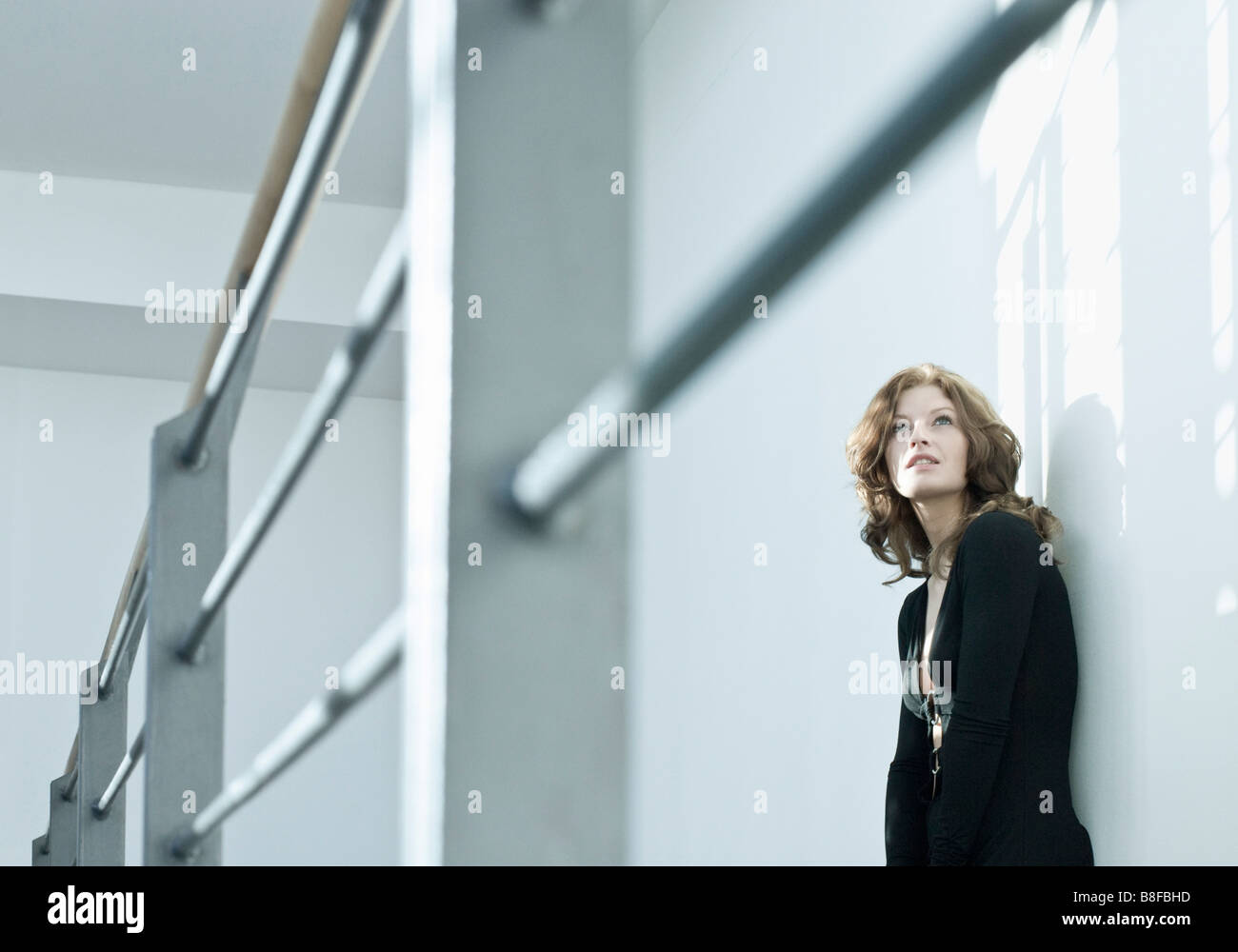 Young woman leaning against wall tout en regardant vers le haut Photo Stock