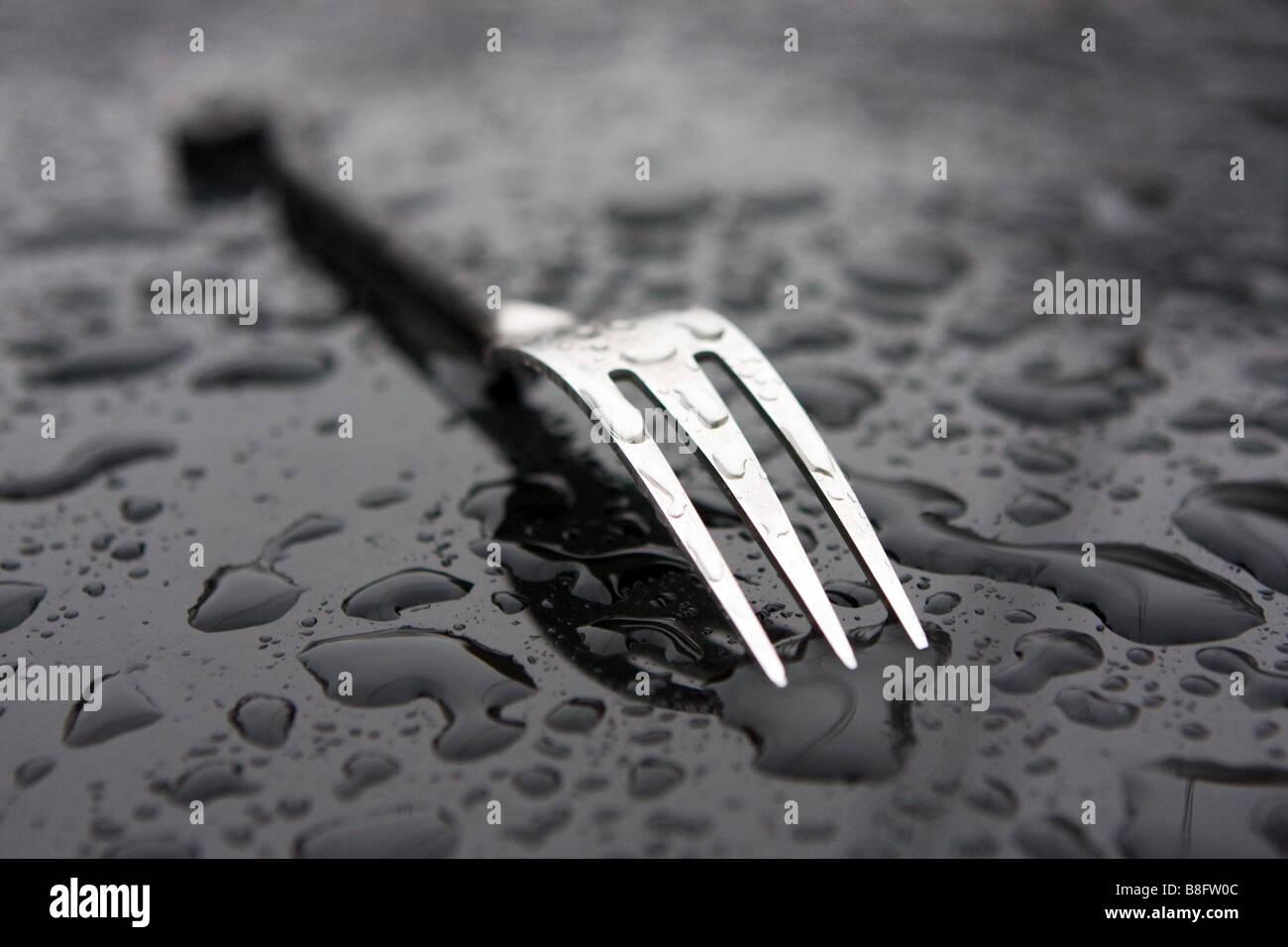 Une fourchette à dîner sur une surface métallique lisse avec des gouttes de pluie Photo Stock