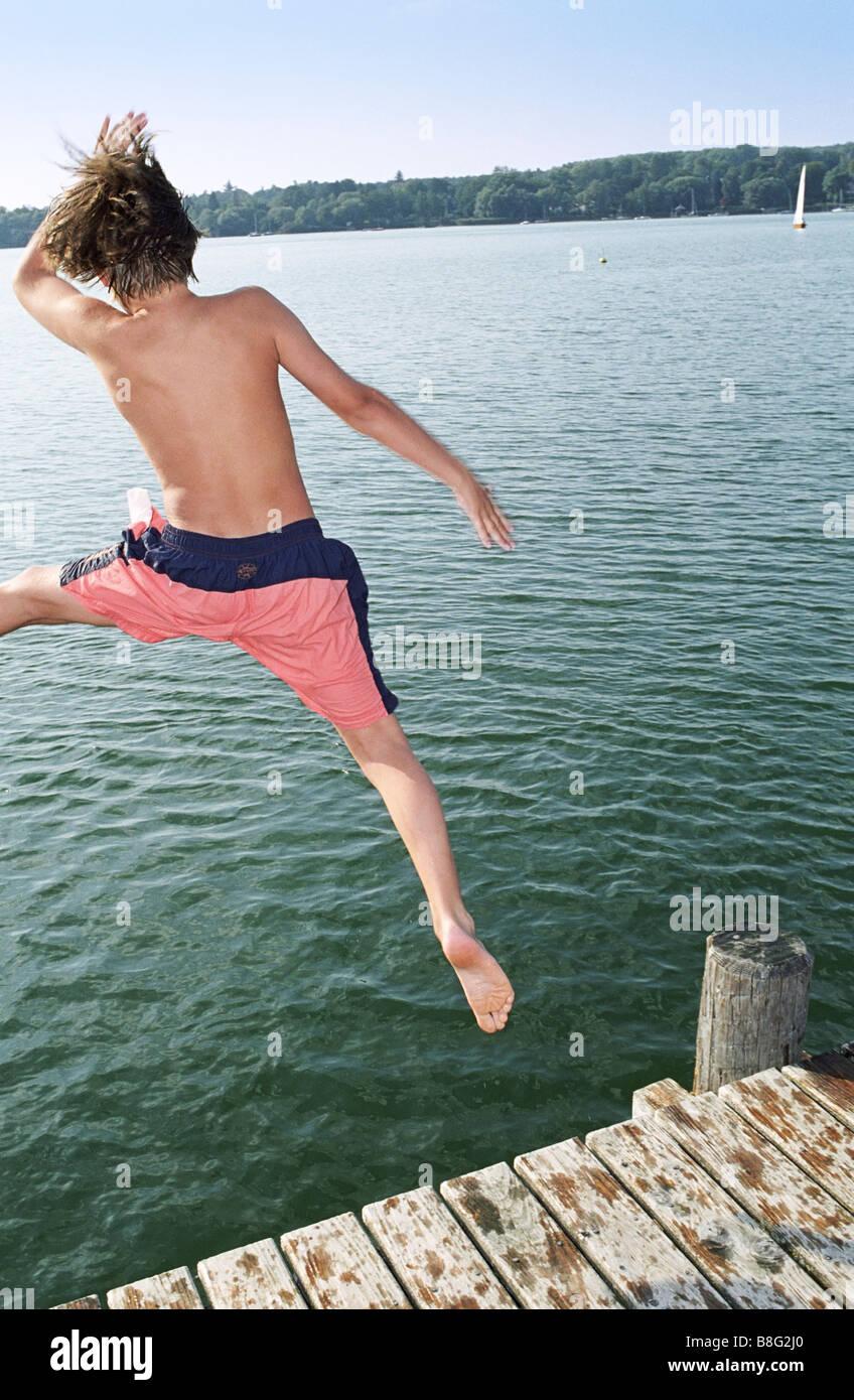 Jeune garçon plongeant dans l'eau d'une passerelle en bois - Salutations - Fun - Été - Piscine Photo Stock