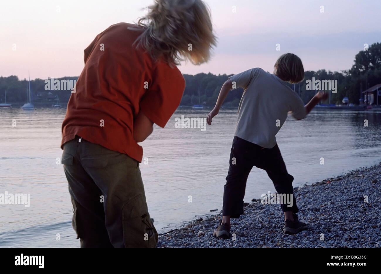 Deux garçons lançant des pierres plates sur la surface de l'eau - intelligence - Jeu - l'amitié - Lac - Crépuscule Banque D'Images