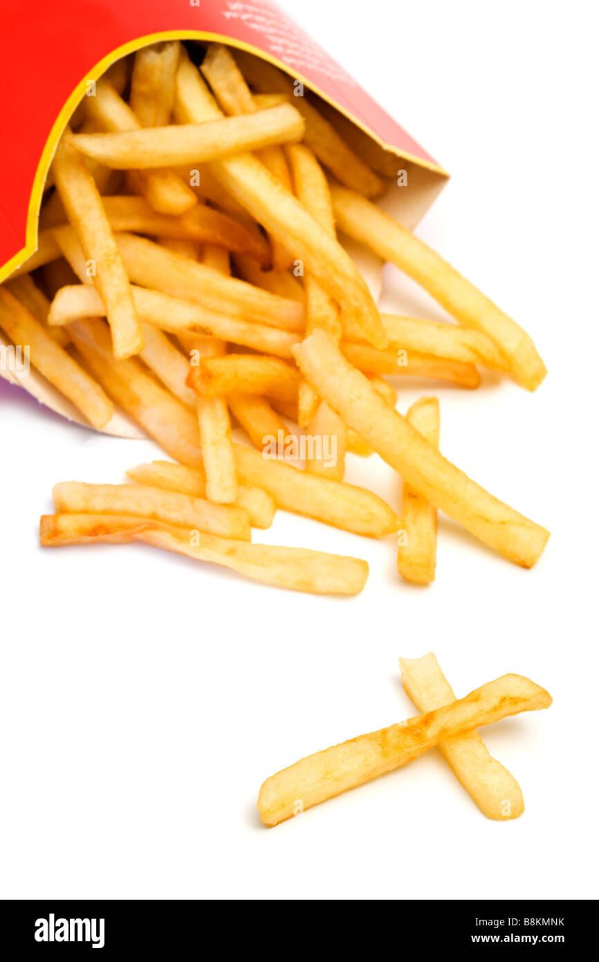Fast food malsaine. Frites tombant de carton fort incliné, deux pièces qui ressemble à une croix, Photo Stock