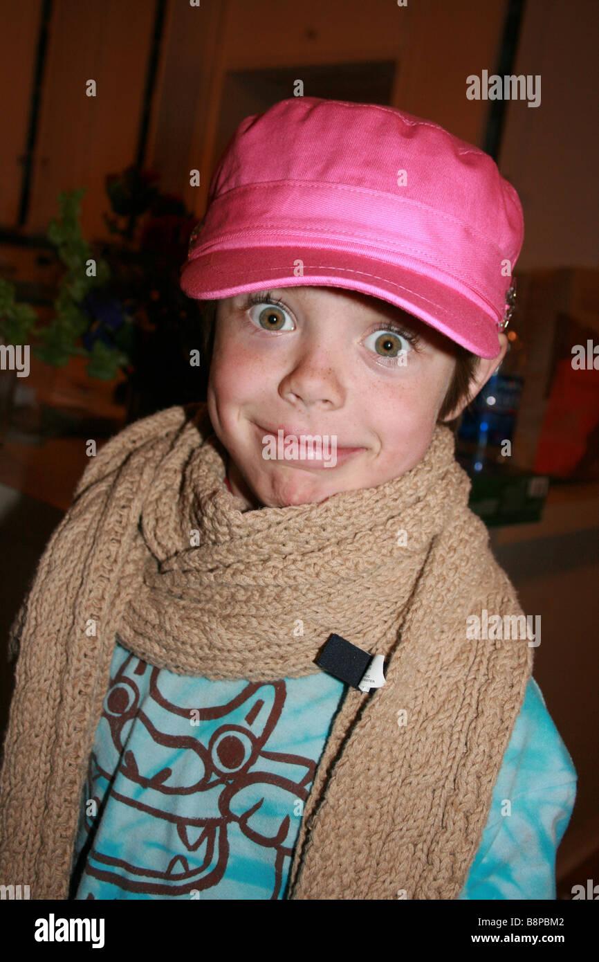 Six ans garçon habillé en fille portant un chapeau rose et rouge à lèvres Photo Stock