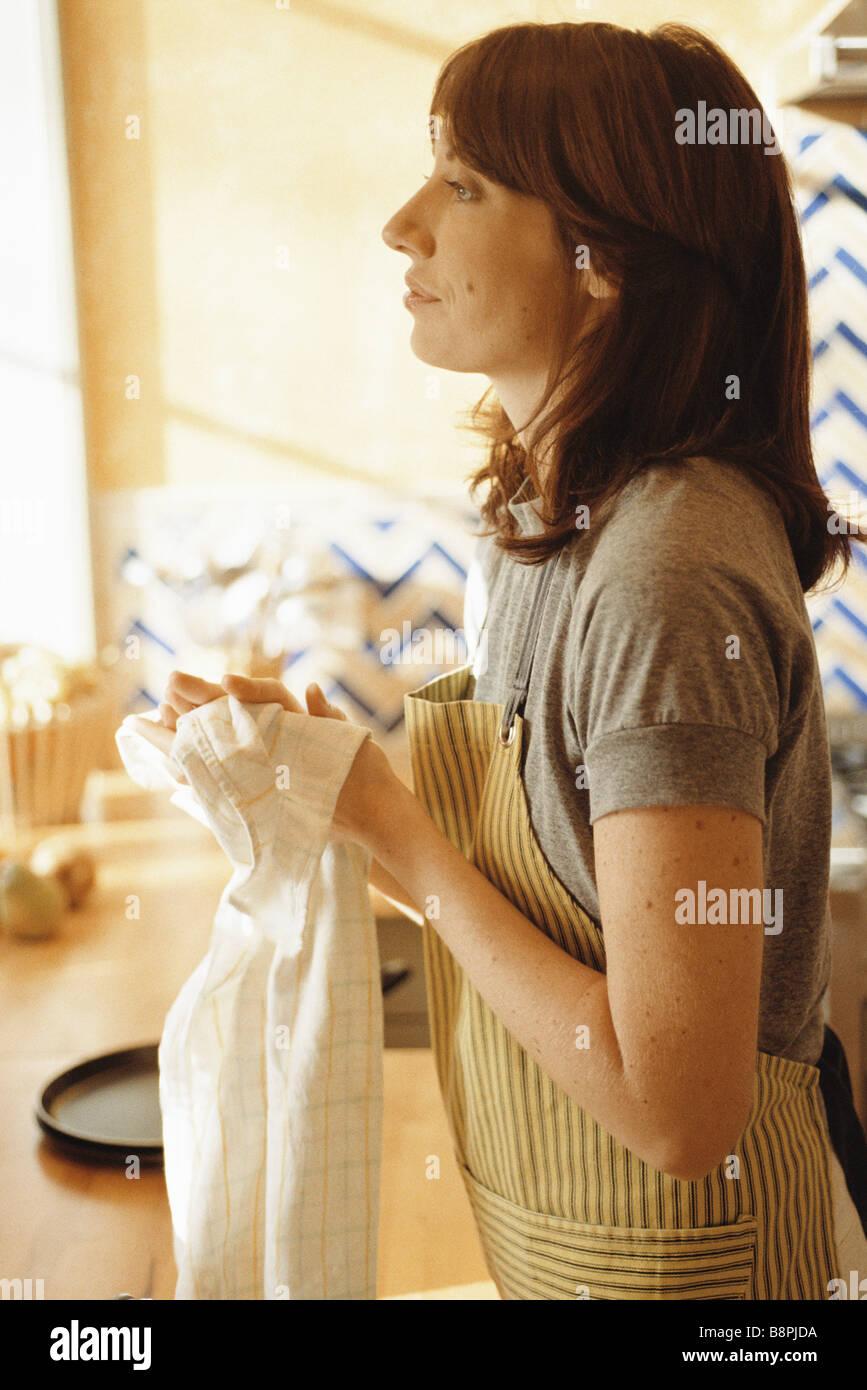 Femme debout dans la cuisine, se sécher les mains et les yeux dans la distance Photo Stock