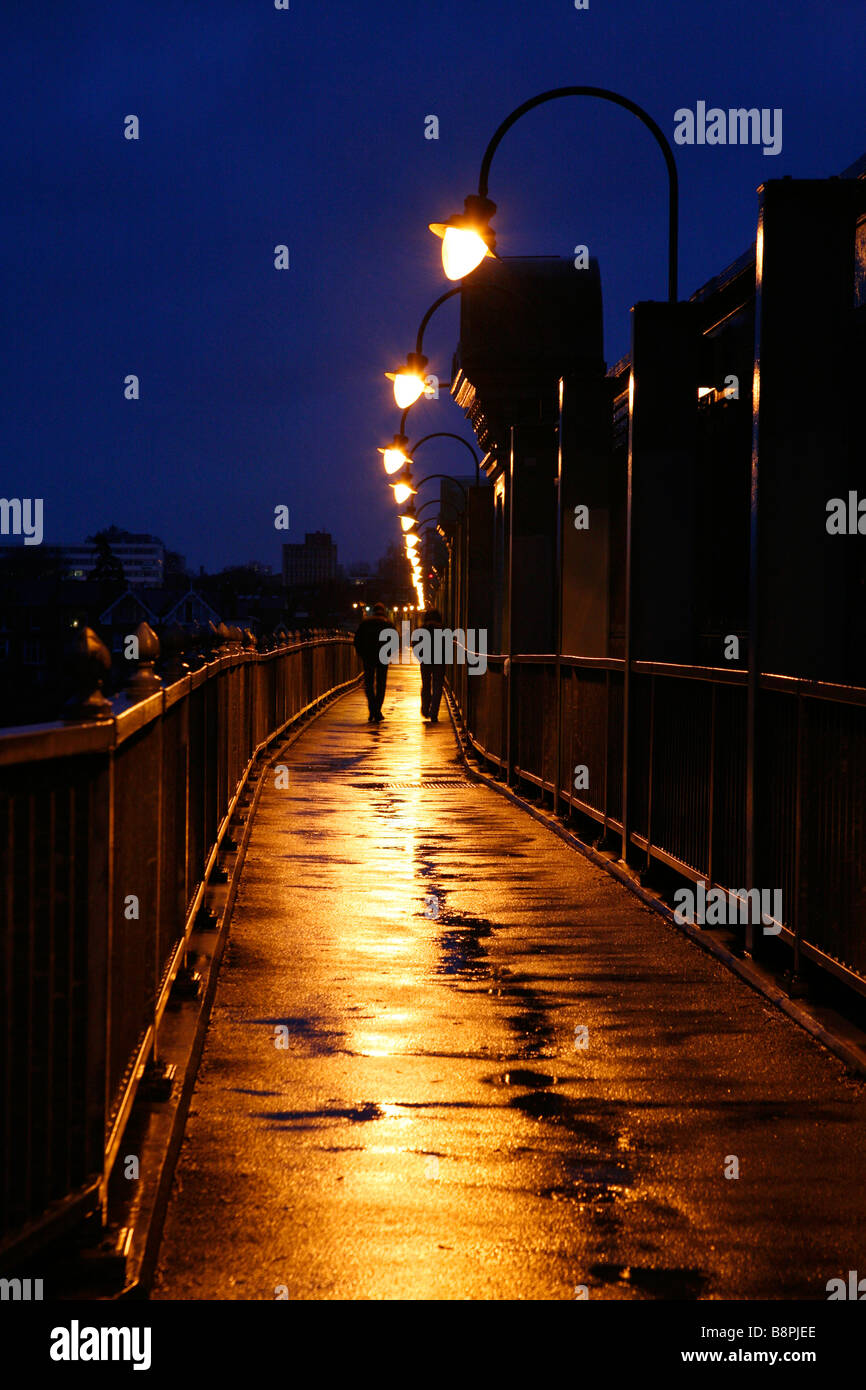 Les piétons marchant sur un pont ferroviaire Fulham humide, Fulham, London Photo Stock