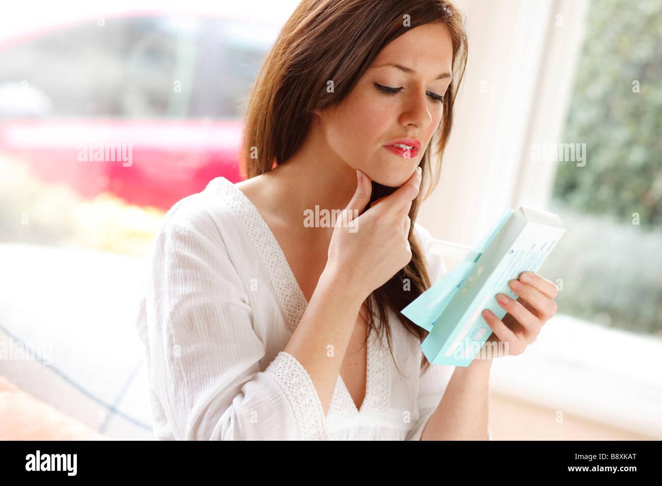 Femme à la recherche de résultats de test de grossesse Photo Stock
