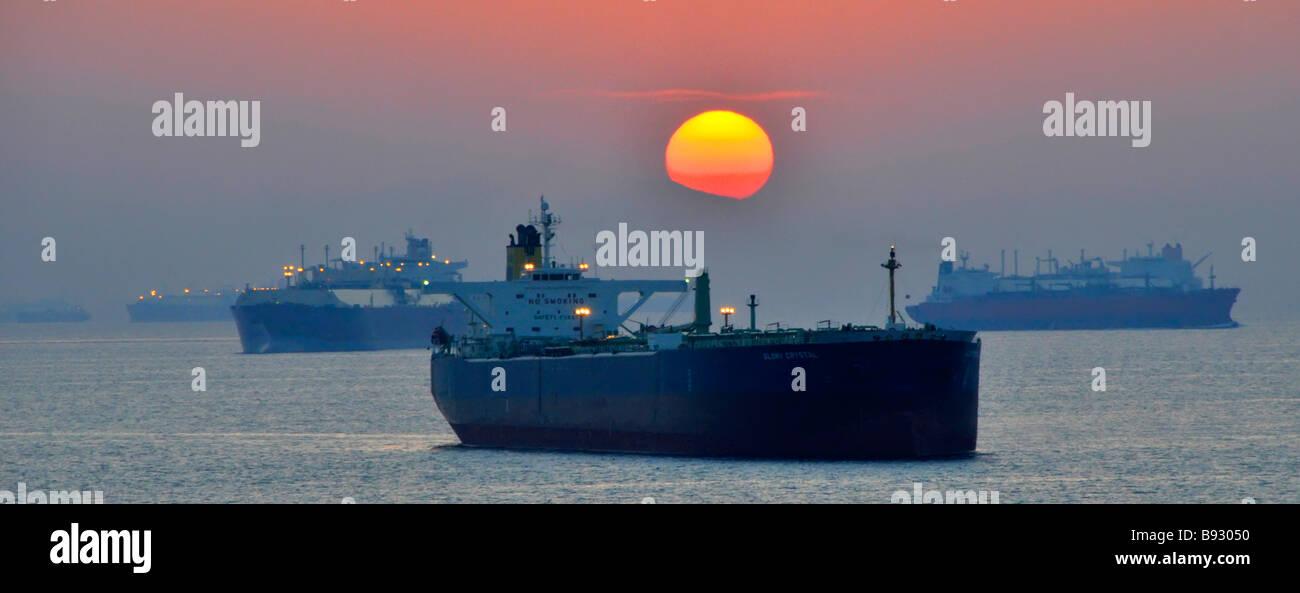 Coucher du soleil haze & voyage y compris les vraquiers et les pétroliers en mer mouillage au large des côtes de Californie Golfe d'Oman, près de Détroit d'Ormuz au Moyen-Orient Banque D'Images