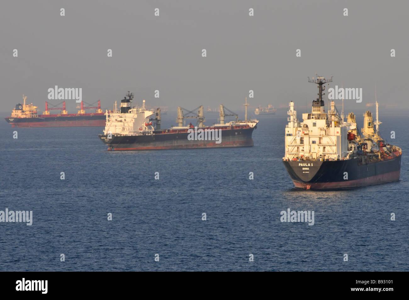 Navires à vide y compris des vraquiers et des pétroliers à l'ancre au large des côtes de Dubaï dans le golfe d'Oman, près de Détroit d'Ormuz vue dans le lointain de la brume sèche Banque D'Images