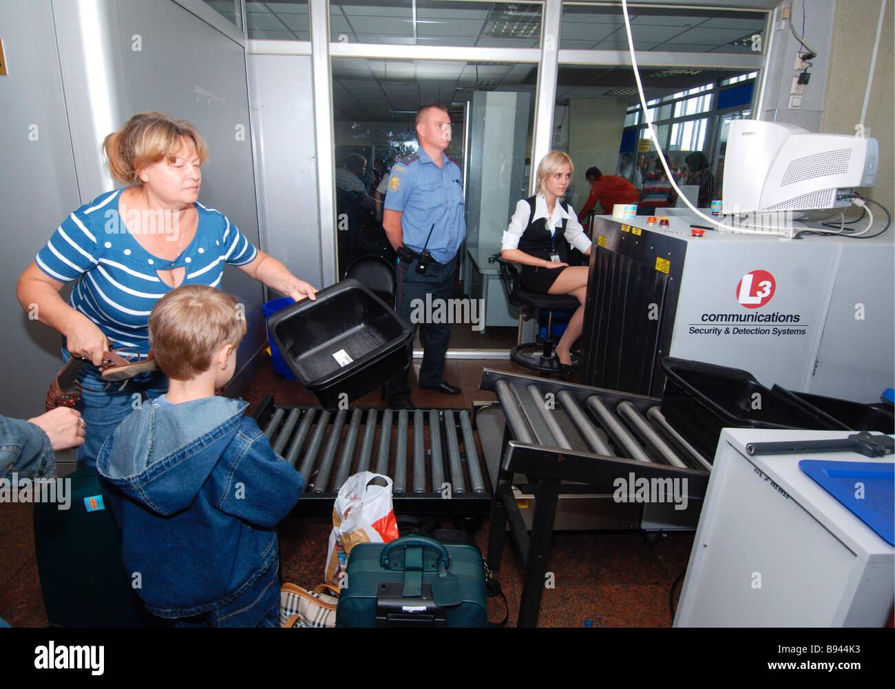 Les passagers à pied par le biais de détecteurs de métaux et de leurs bagages est scannée à Photo Stock