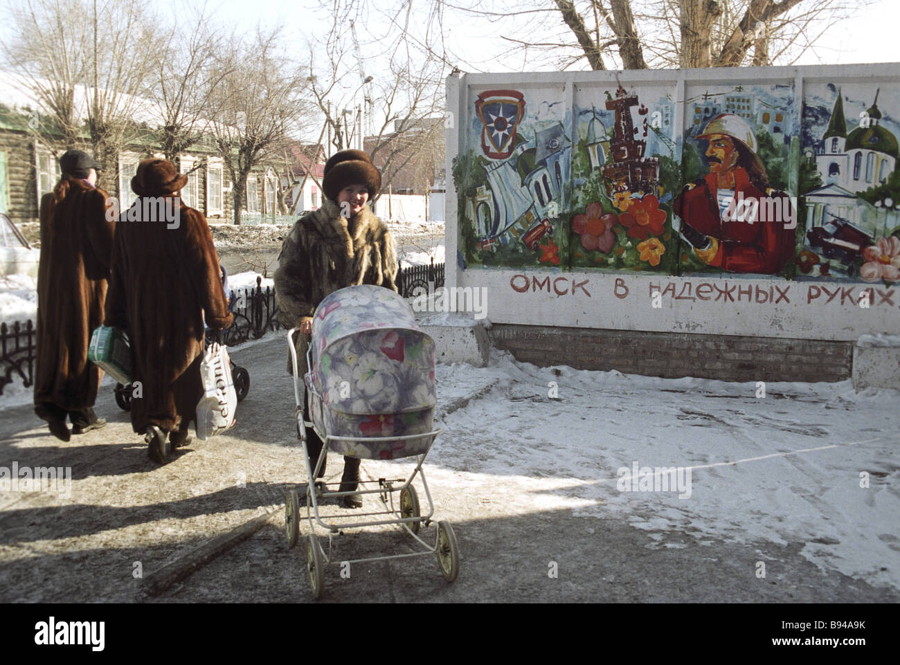 Une femme pousse un landau le long d'une rue à Omsk Banque D'Images