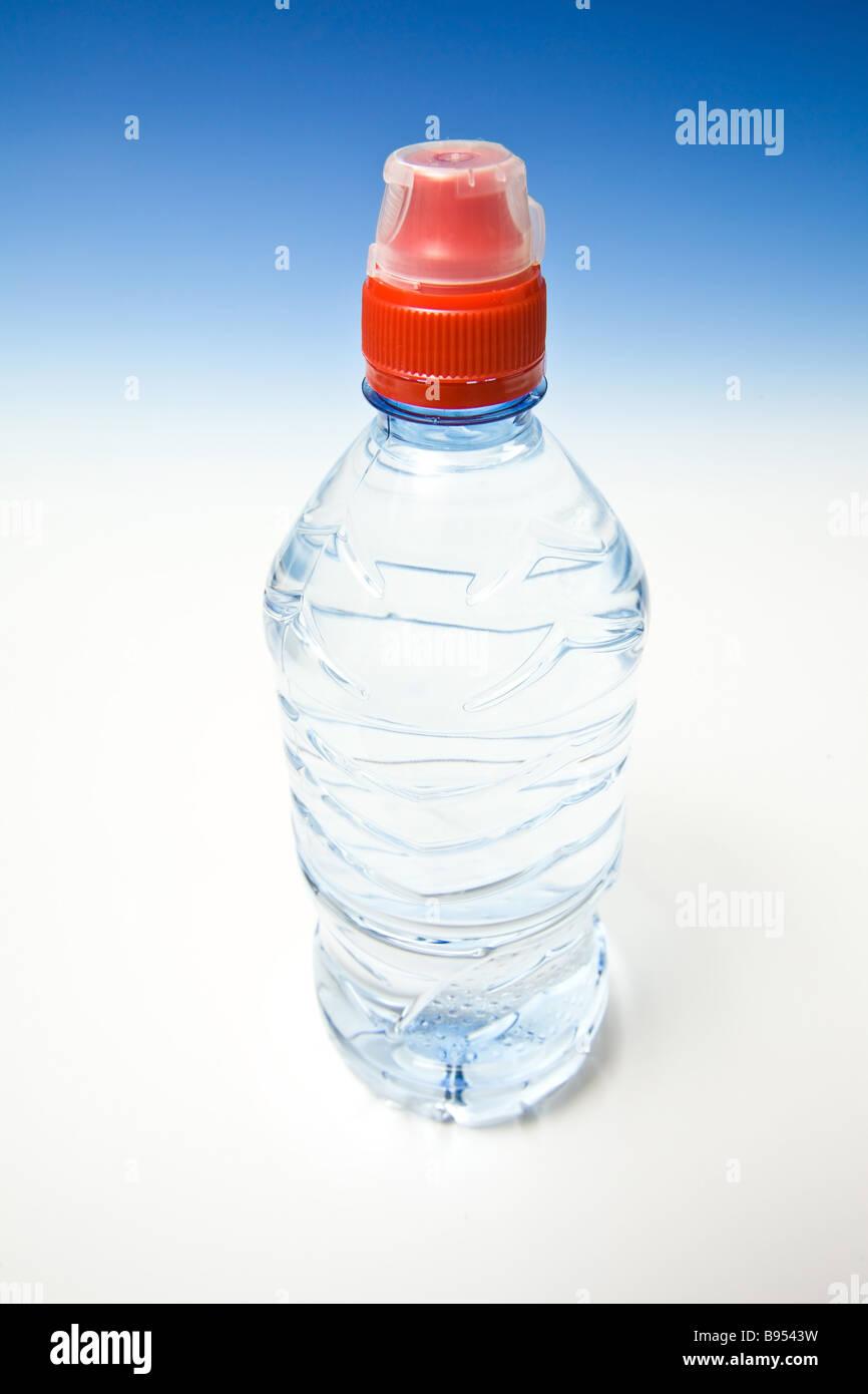 L'eau en bouteille sur un fond bleu dégradé studio Photo Stock