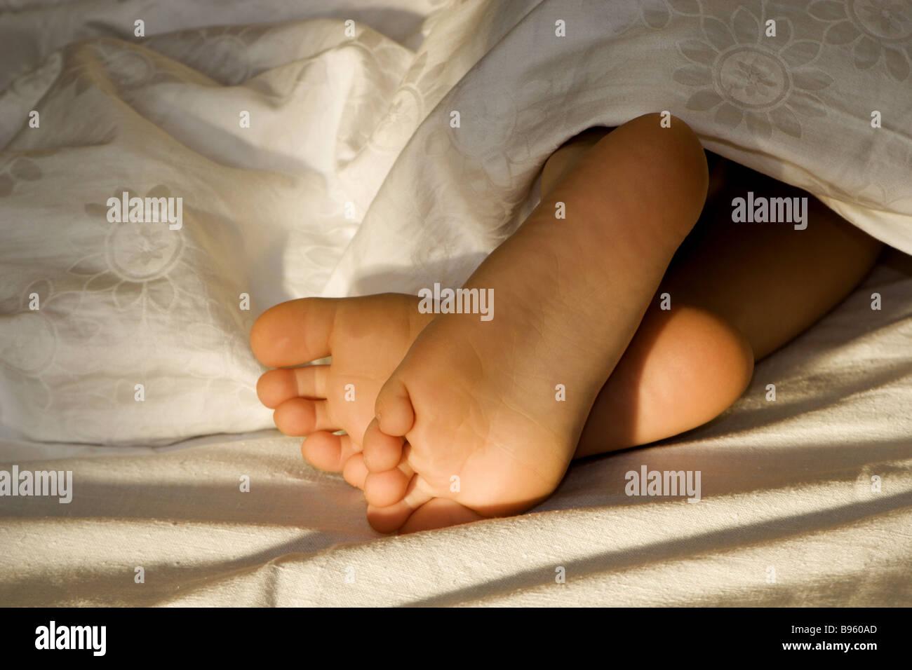 Pieds d'enfant dans le lit - matin Photo Stock
