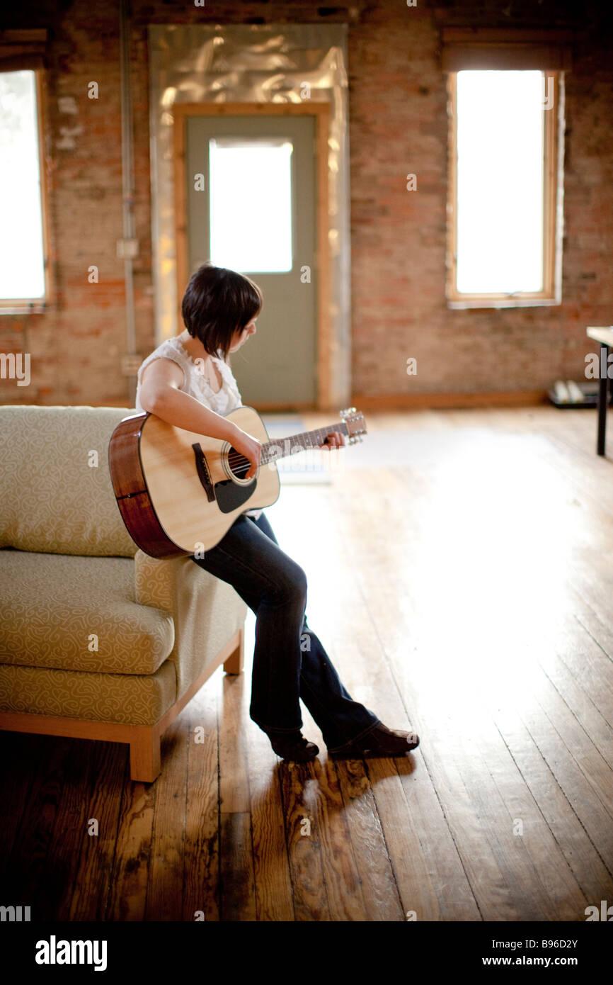 Jeune femme jouant de la guitare dans l'espace urbain Photo Stock