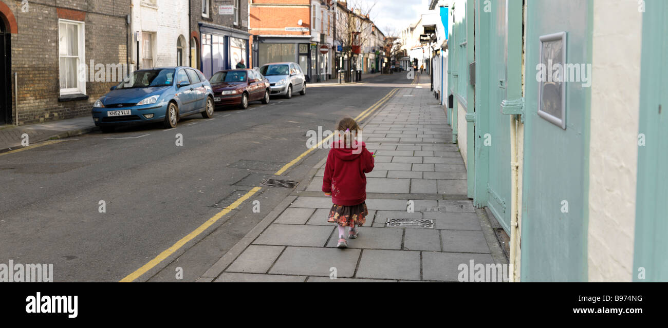 Petite fille de cinq ans marche dans une rue de Salisbury Wiltshire Photo Stock