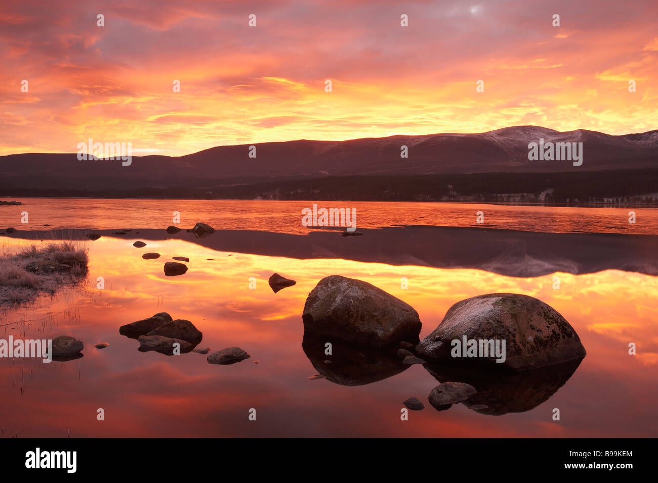 Le Loch Morlich et montagnes de Cairngorm à l'aube Photo Stock