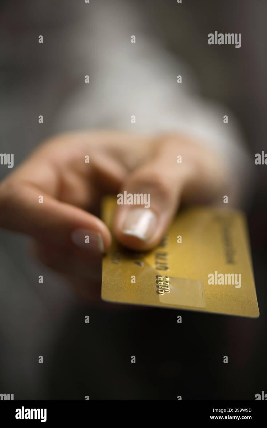 Woman's hand holding out carte de crédit, extreme close-up Photo Stock