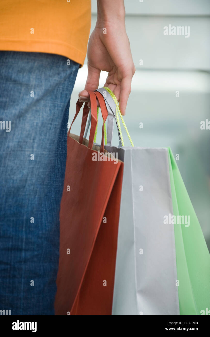 Woman's hand holding shopping bags, close-up Photo Stock
