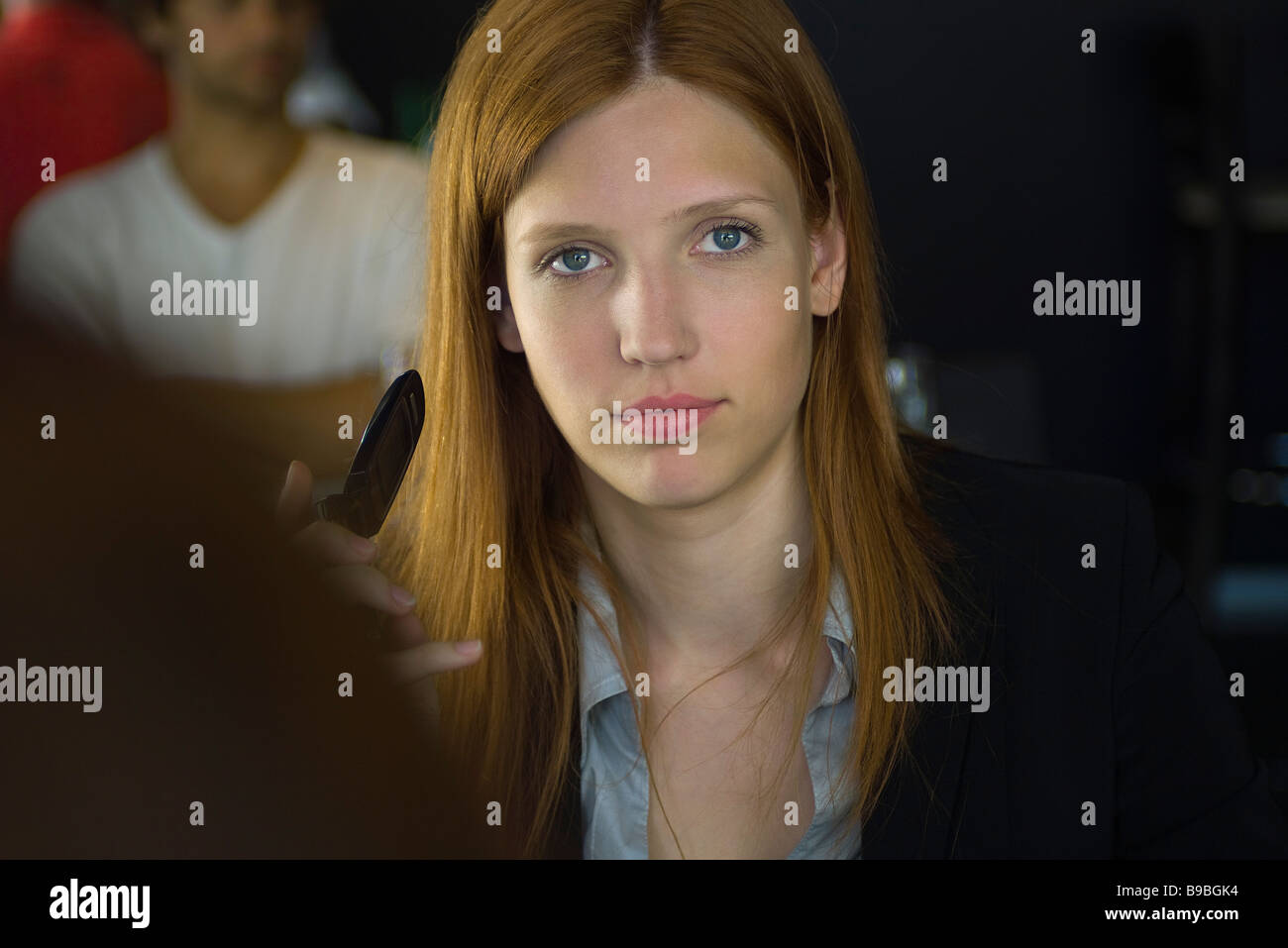 Woman holding cell phone, regardant at camera Banque D'Images