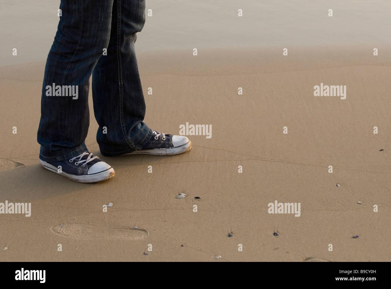 Partie inférieure d'un homme portant des chaussures Converse formateurs à pied par la plage Beyrouth Photo Stock