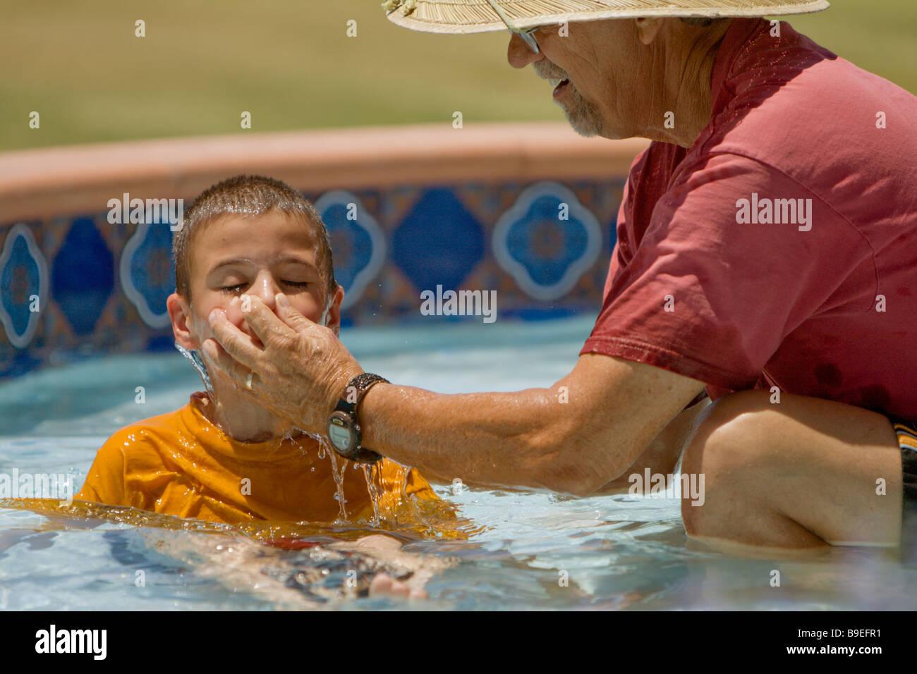 Le pasteur baptisant un garçon Photo Stock