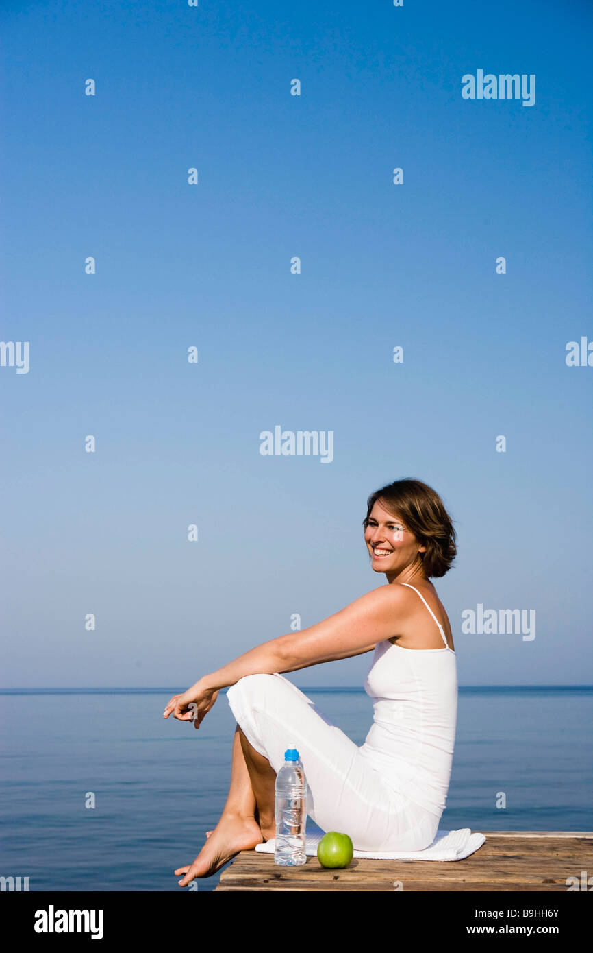 Femme assise sur un quai Photo Stock