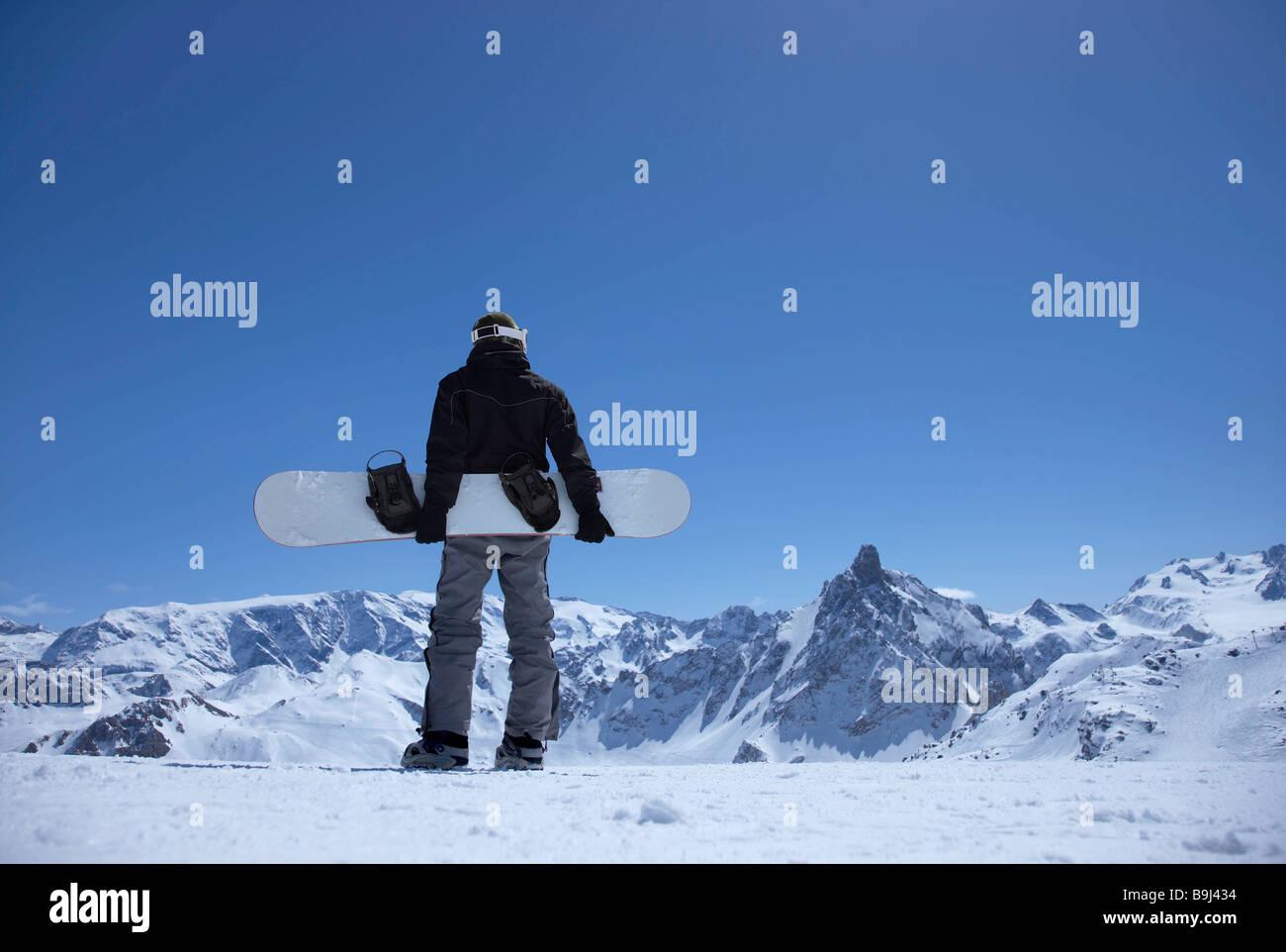 Homme debout sur la montagne avec snowboard Photo Stock