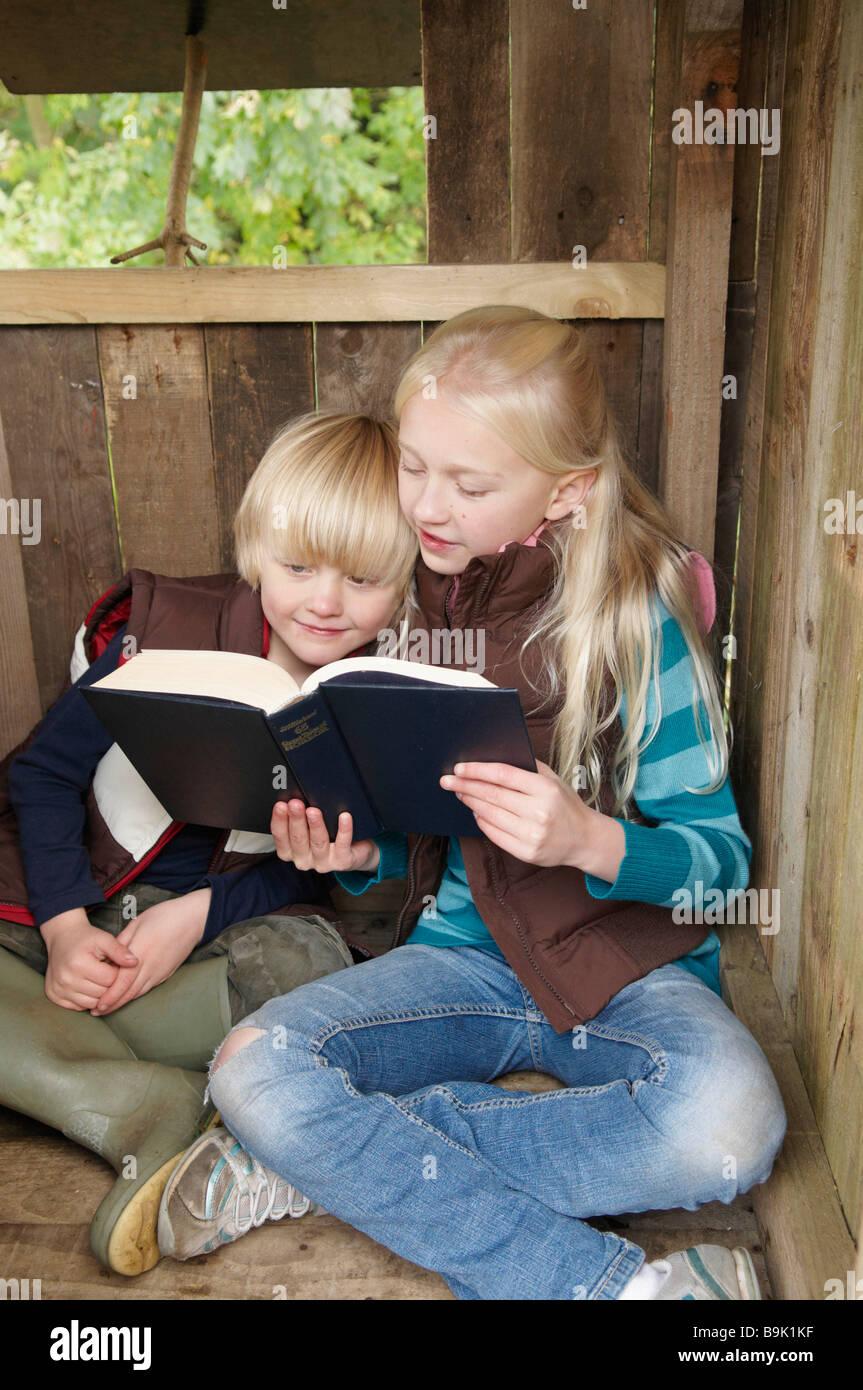 Girl reading histoire de jeune garçon Photo Stock