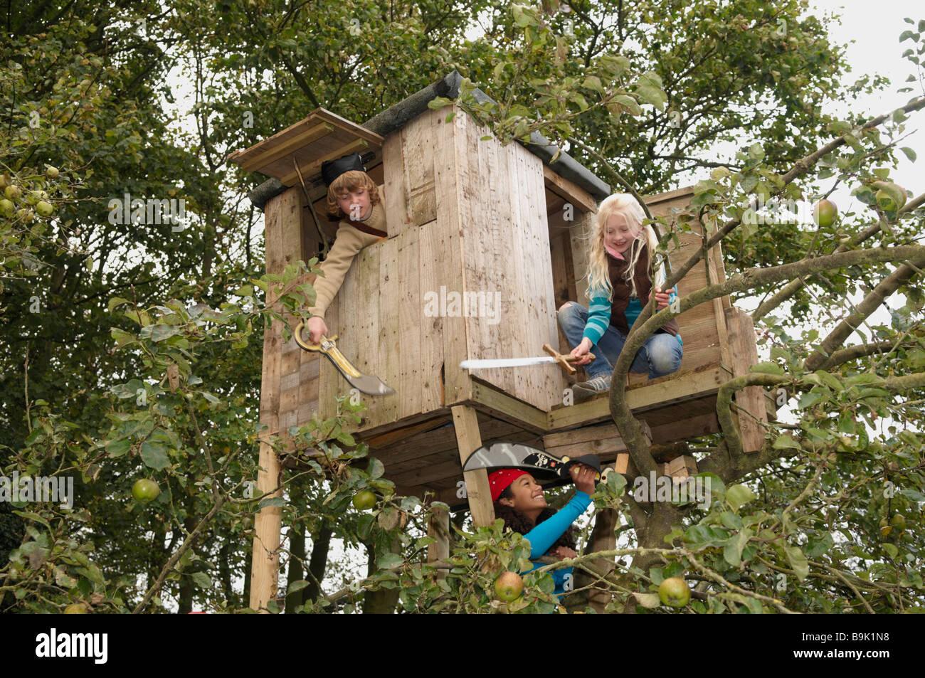 Enfants jouant dans treehouse Banque D'Images